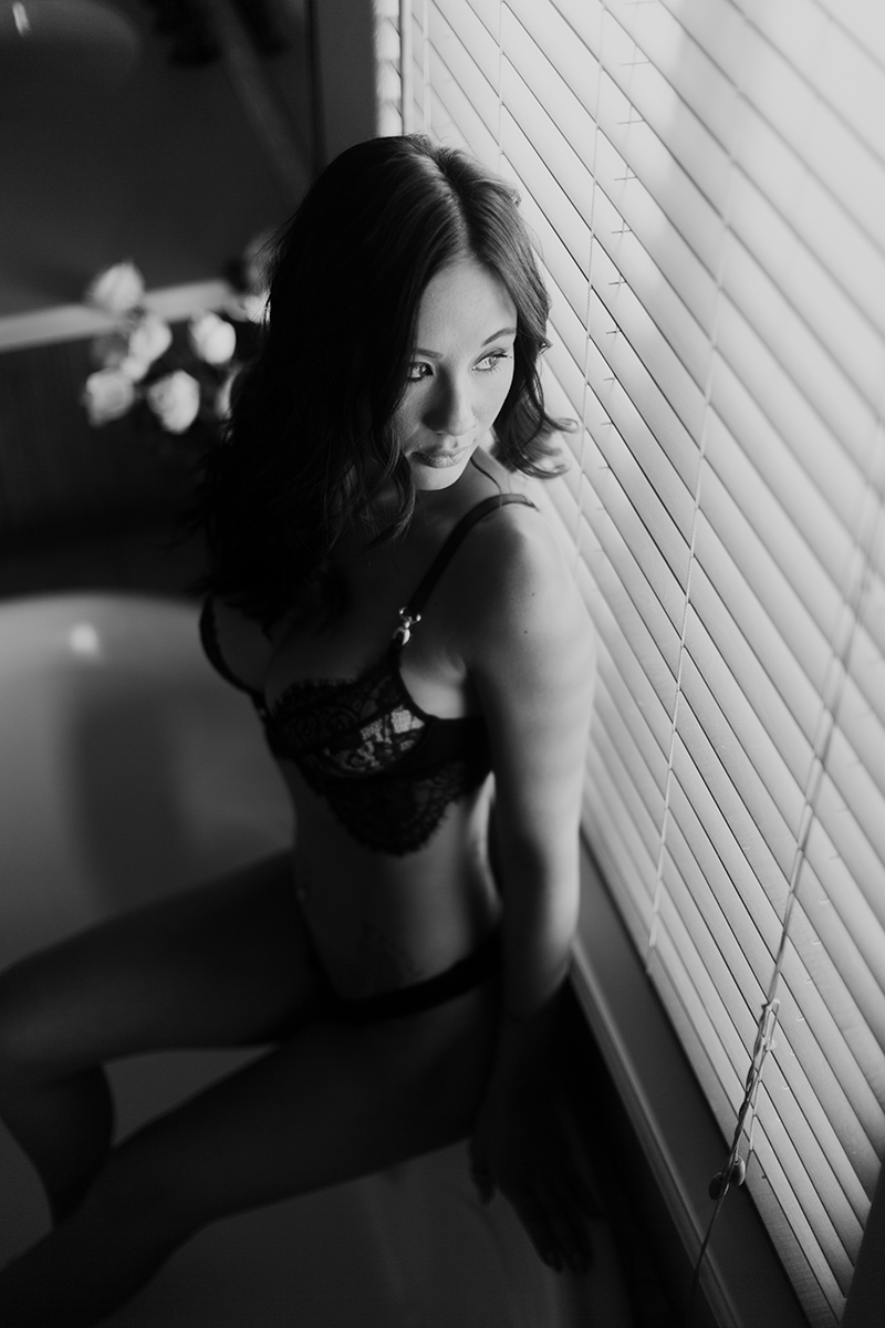 A beautiful brunette woman poses for a Colorado Springs home boudoir photography session wearing a black bra and underwear set sitting on the side of a bathtub in front of a mirror in her bathroom in Colorado