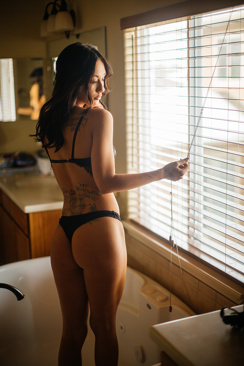 A beautiful brunette woman poses for a Colorado Springs home boudoir photography session wearing a black bra and underwear set standing in a bathtub in front of a mirror in her bathroom in Colorado