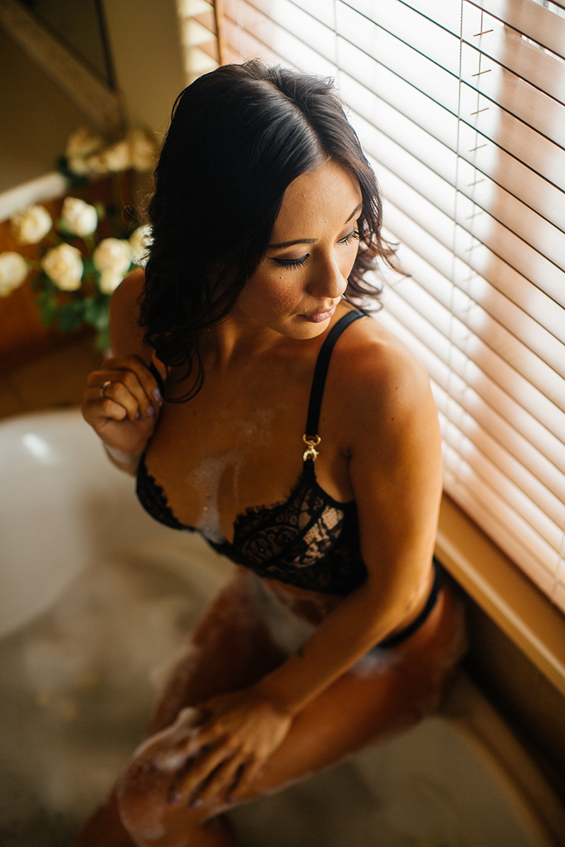 A beautiful brunette woman poses for a Colorado Springs home boudoir photography session wearing a black bra and underwear set sitting on the side of a bubble filled bathtub in front of a mirror in her bathroom in Colorado