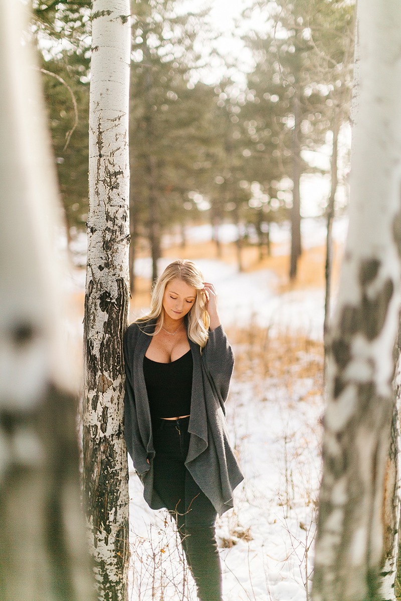 A beautiful young blonde woman posing for a Genesee Park boudoir photography session in the Rocky Mountains wearing black jeans, a black shirt and a gray sweater leaning on an aspen tree in a snow covered field