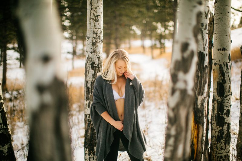 A beautiful young blonde woman posing for a Genesee Park boudoir photography session in the Rocky Mountains wearing black jeans, a white bra and a gray sweater leaning on an aspen tree in a snow covered field