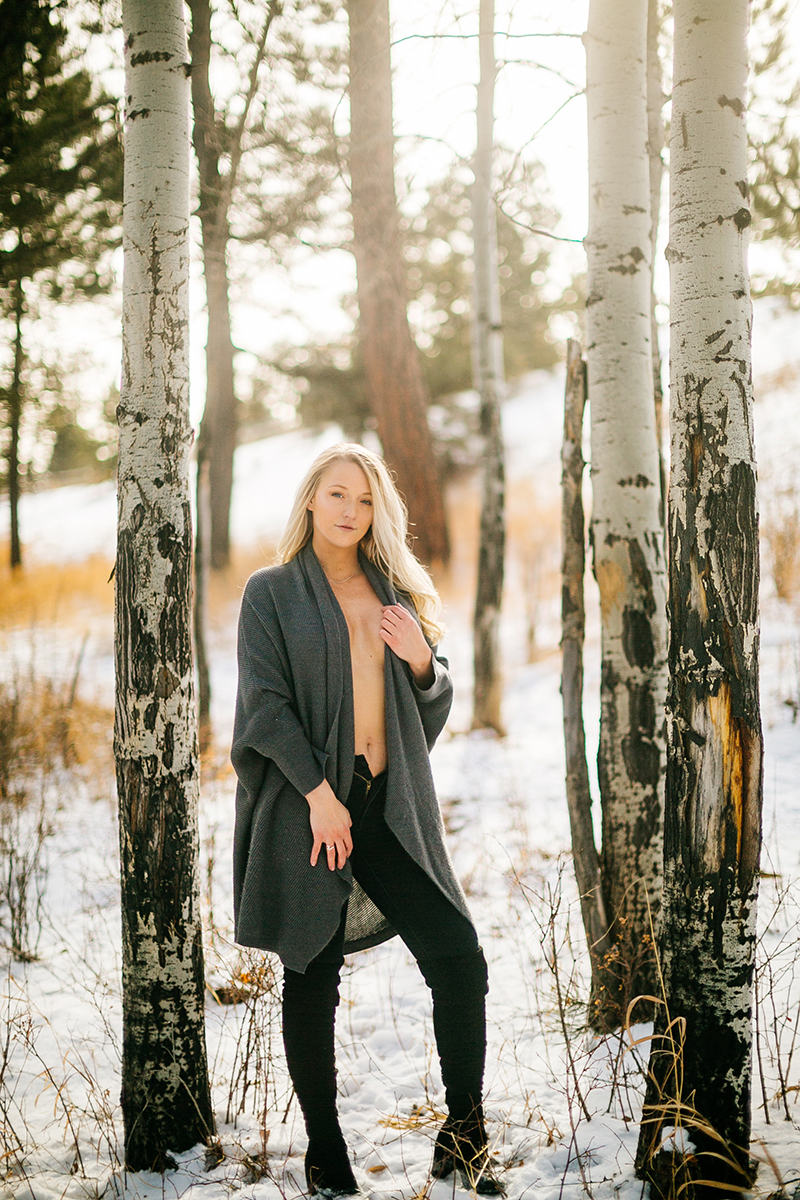 A beautiful young blonde woman posing topless for a Genesee Park boudoir photography session in the Rocky Mountains wearing black jeans and a gray sweater leaning on an aspen tree in a snow covered field