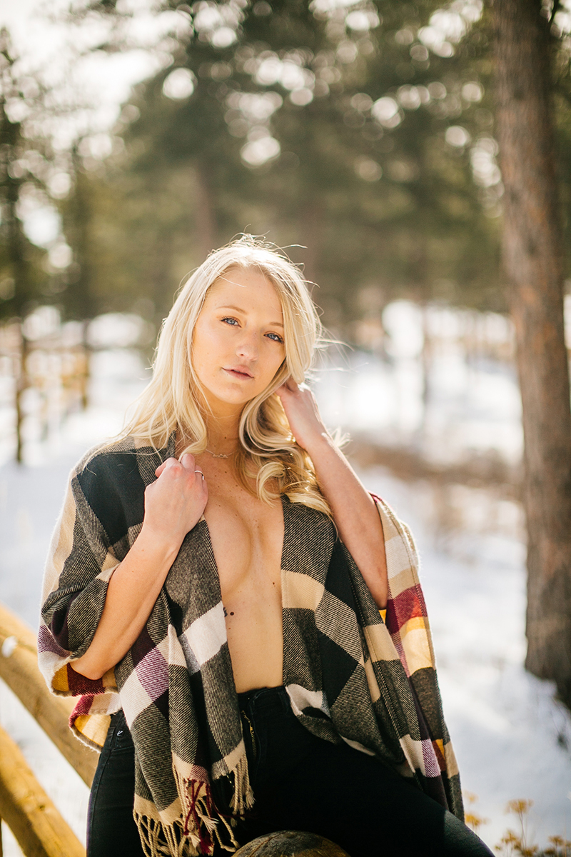 A beautiful young blonde woman posing topless for a Genesee Park boudoir photography session in the Rocky Mountains wearing jeans, boots and a red plaid scarf leaning against a wood fence in a snow covered field