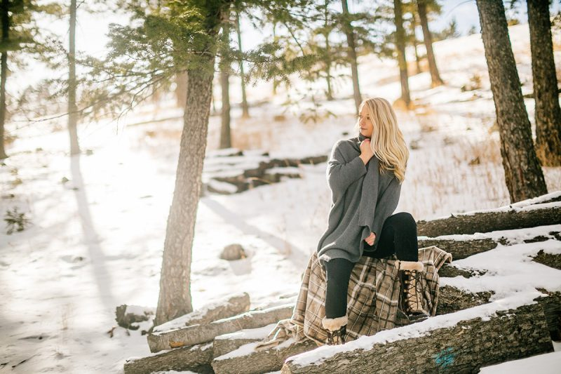A beautiful young blonde woman posing topless for a Genesee Park boudoir photography session in the Rocky Mountains wearing black jeans and a gray sweater sitting on a tree stump covered with a plaid blanket in a snow covered field