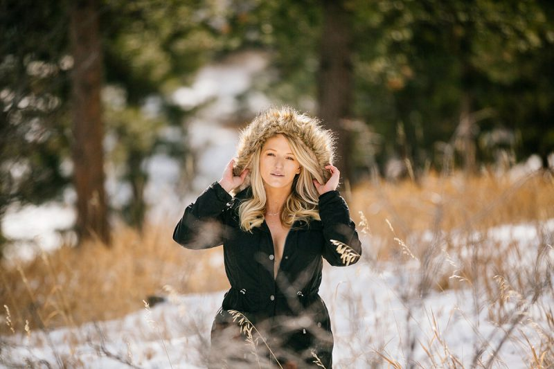 A beautiful young blonde woman posing topless for a Genesee Park boudoir photography session in the Rocky Mountains wearing a black jacket with a fur hood in a snow covered field