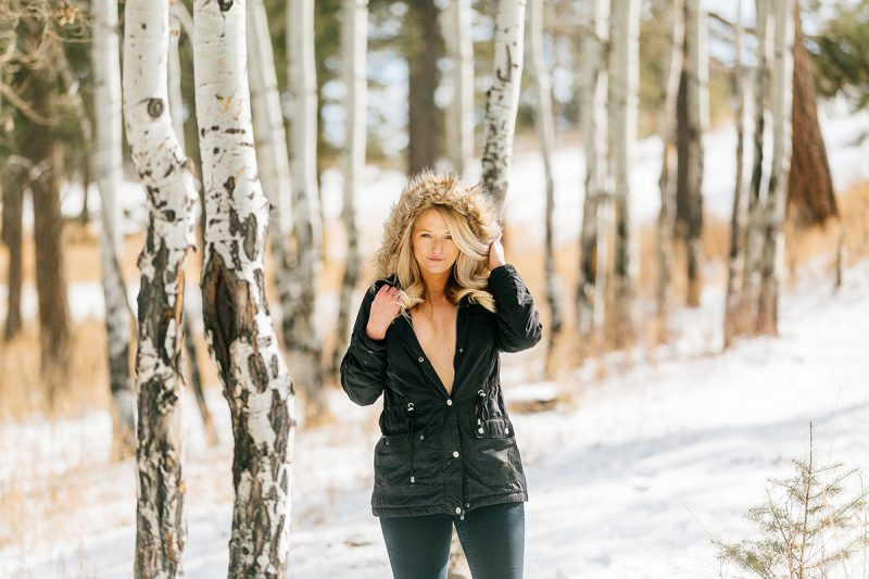 A beautiful young blonde woman posing topless for a Genesee Park boudoir photography session in the Rocky Mountains wearing a black jacket with a fur hood in a snow covered field surrounded by aspens