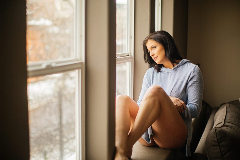 A beautiful young brunette woman poses for a Denver apartment boudoir photography session in her home in Colorado wearing a gray sweater with gray and white underwear sitting in her window