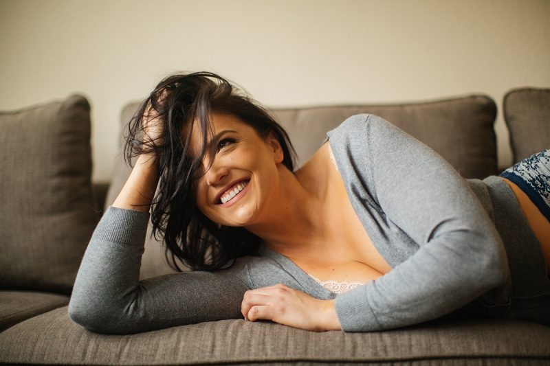 A beautiful young brunette woman poses for a Denver apartment boudoir photography session in her home in Colorado wearing a gray sweater with gray and white underwear laying on her living room carpet