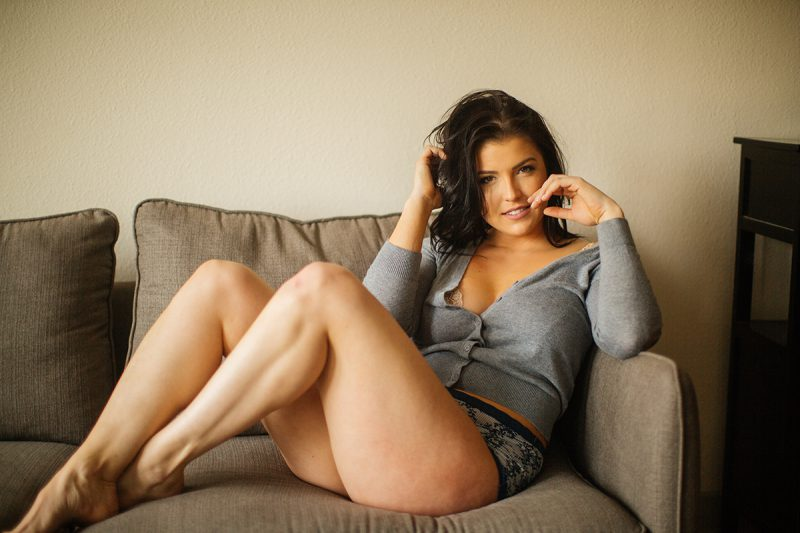 A beautiful young brunette woman poses for a Denver apartment boudoir photography session in her home in Colorado wearing a gray sweater with gray and white underwear sitting on her living room couch