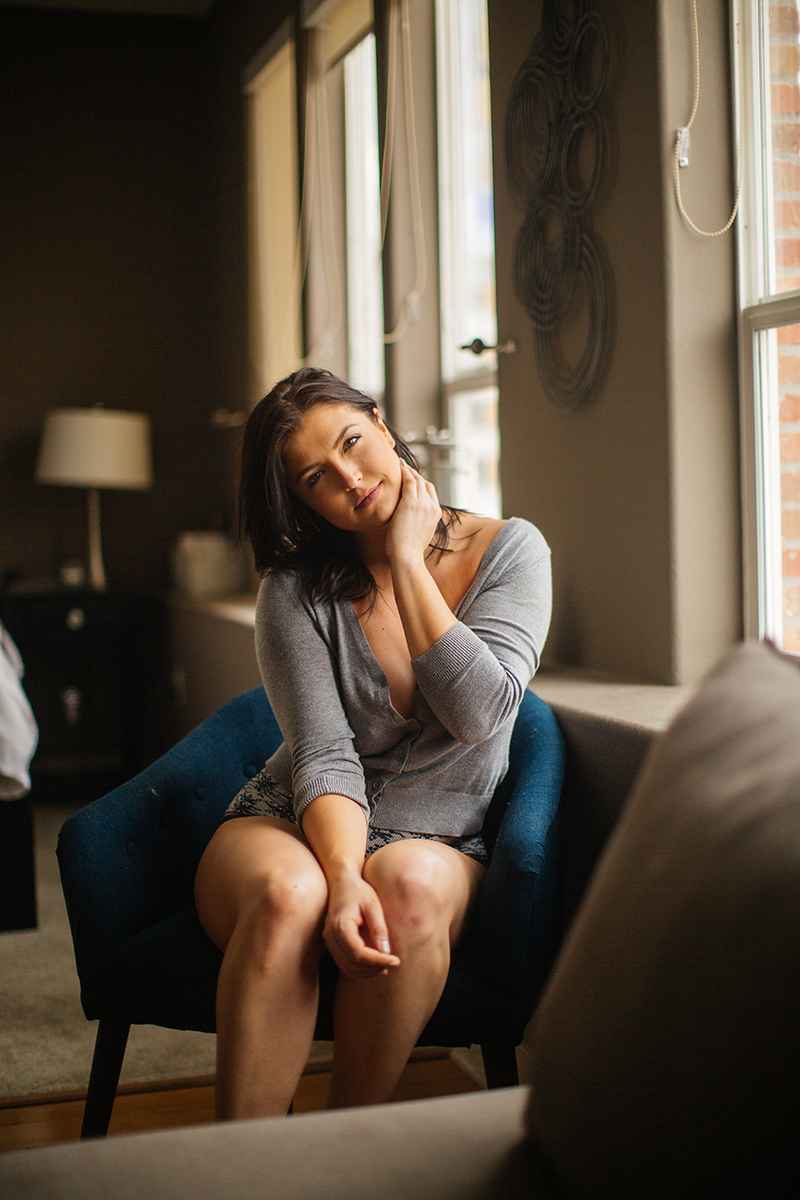 A beautiful young brunette woman poses for a Denver apartment boudoir photography session in her home in Colorado wearing a gray sweater with gray and white underwear sitting on her chair in the living room in front of her big windows