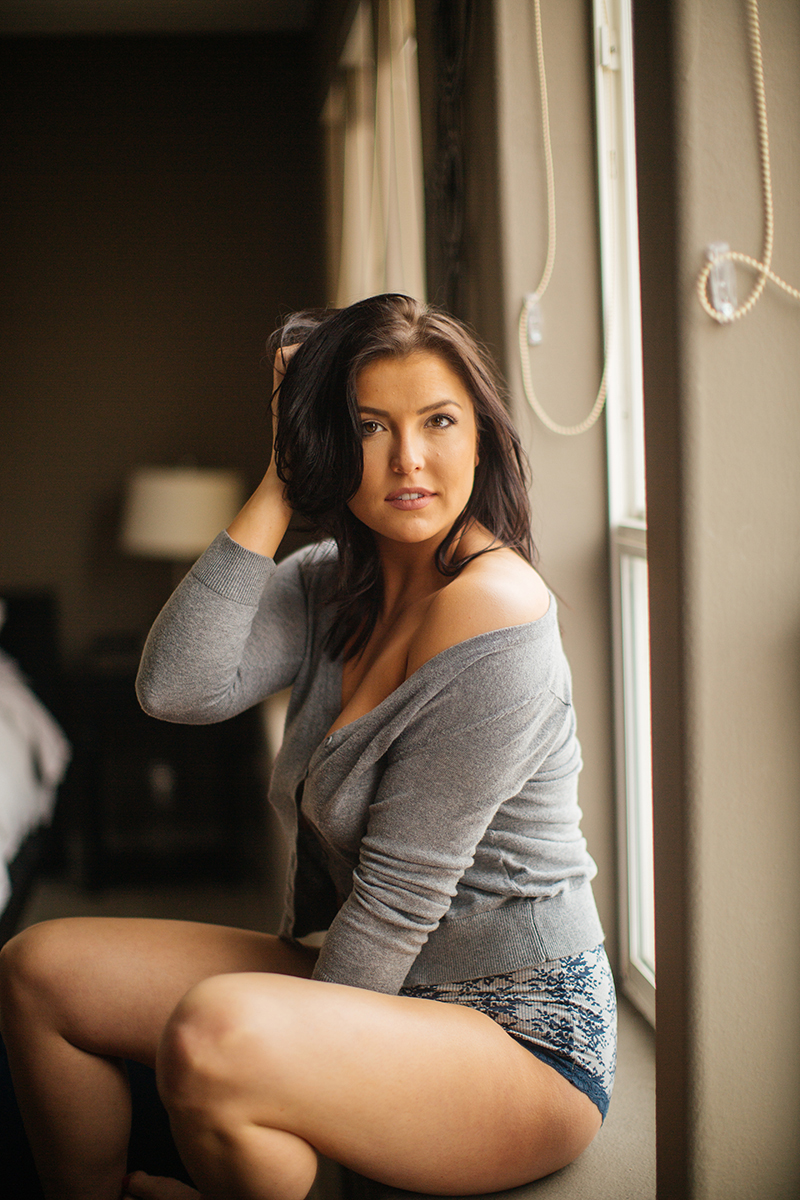 A beautiful young brunette woman poses for a Denver apartment boudoir photography session in her home in Colorado wearing a gray sweater with gray and white underwear sitting in front of her windows