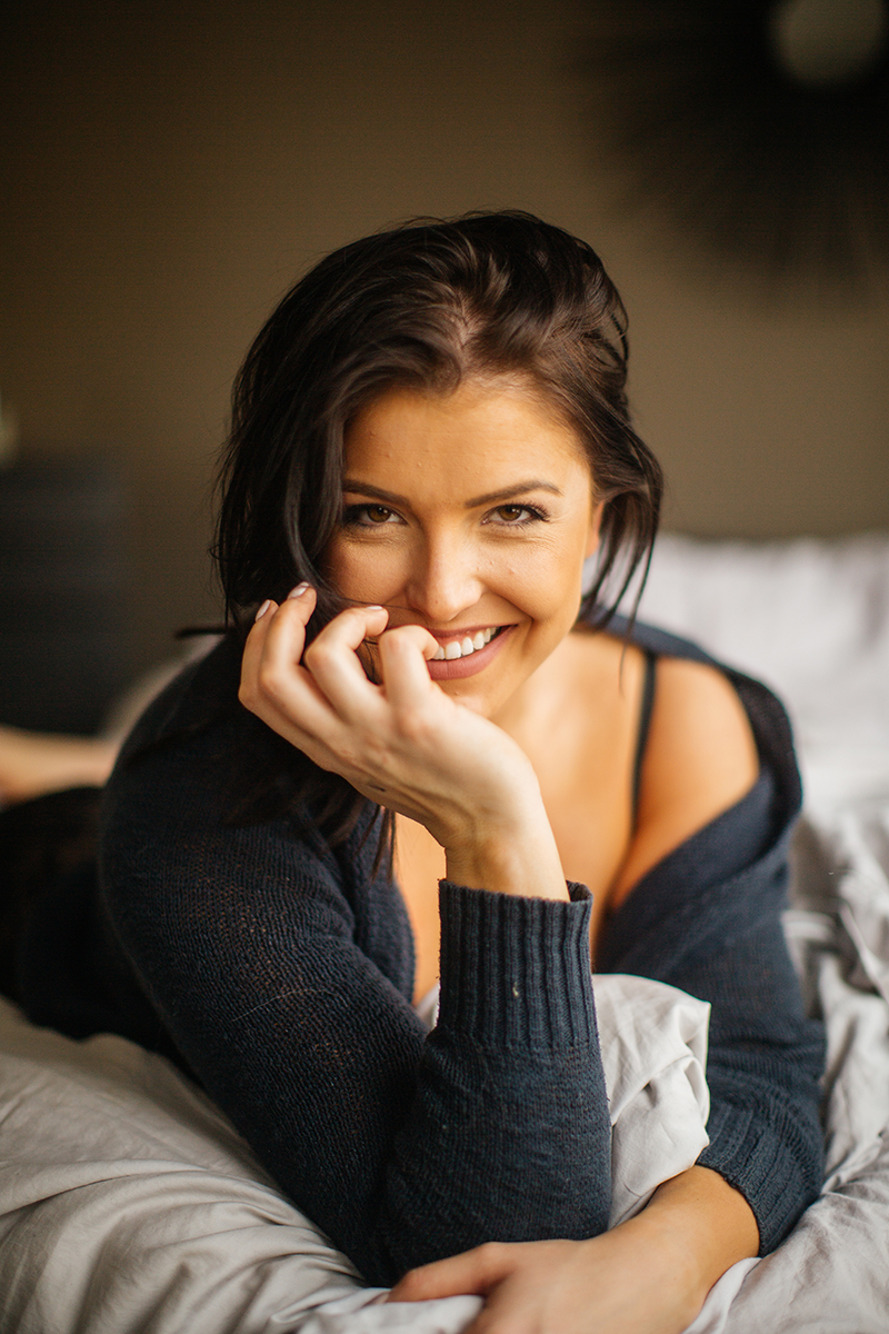 A beautiful young brunette woman poses for a Denver apartment boudoir photography session in her home in Colorado wearing a blue sweater, black bra and underwear set laying on on her bed with blankets