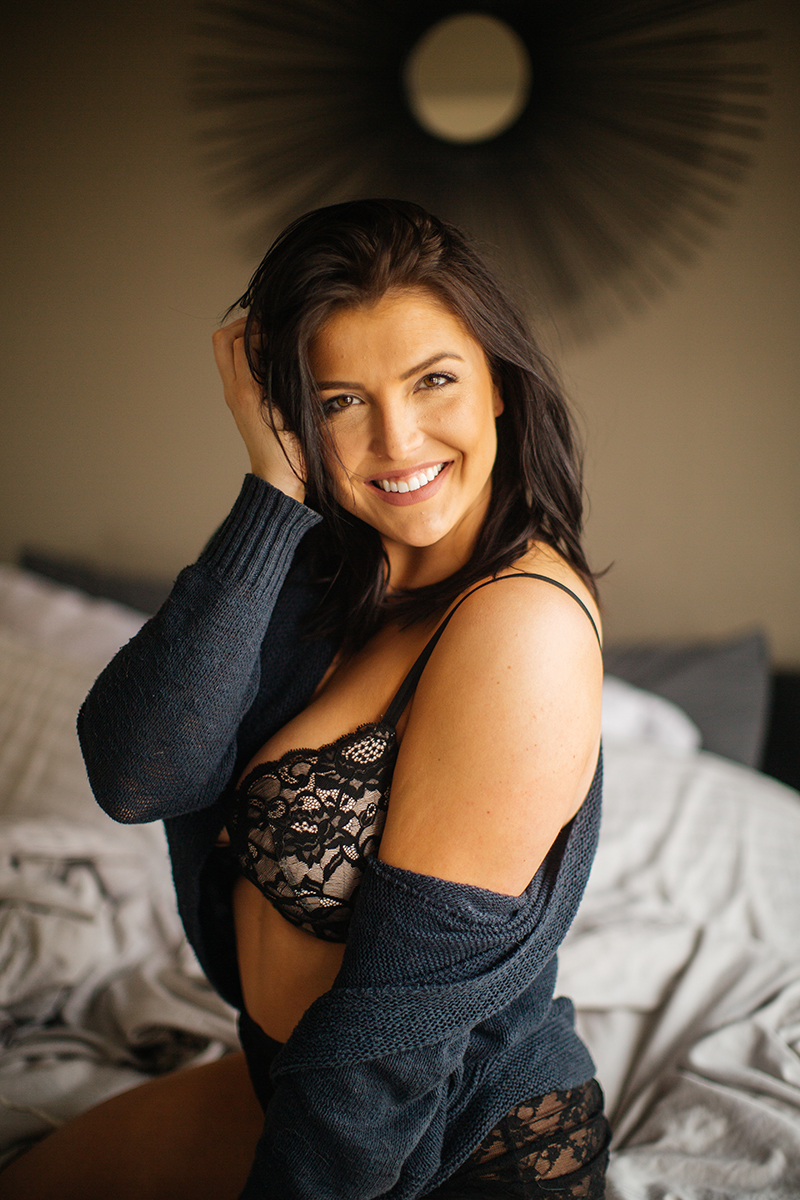 A beautiful young brunette woman poses for a Denver apartment boudoir photography session in her home in Colorado wearing a blue sweater, black bra and underwear set sitting on on her bed with blankets