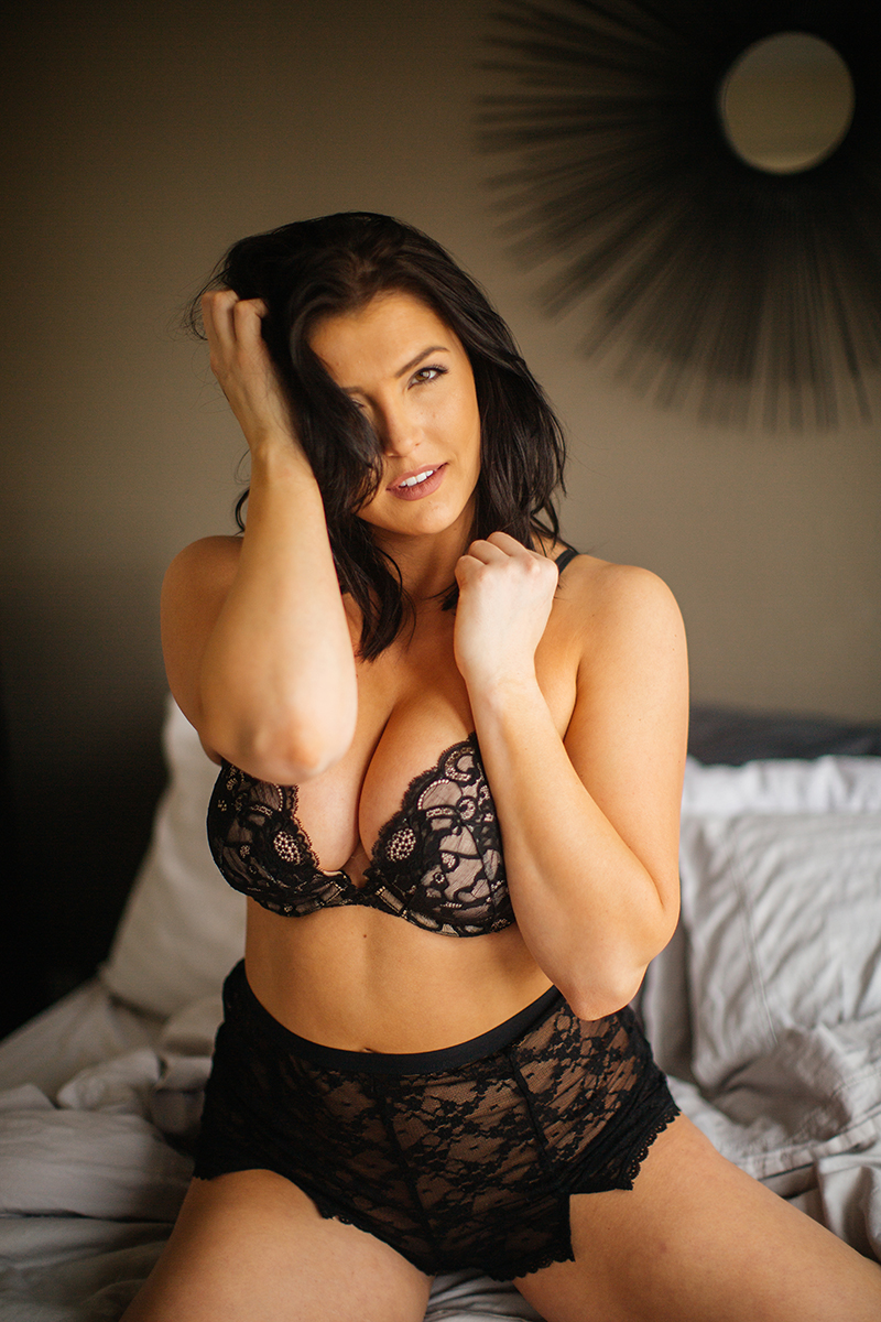 A beautiful young brunette woman poses for a Denver apartment boudoir photography session in her home in Colorado wearing a black bra and underwear set sitting on on her bed with blankets