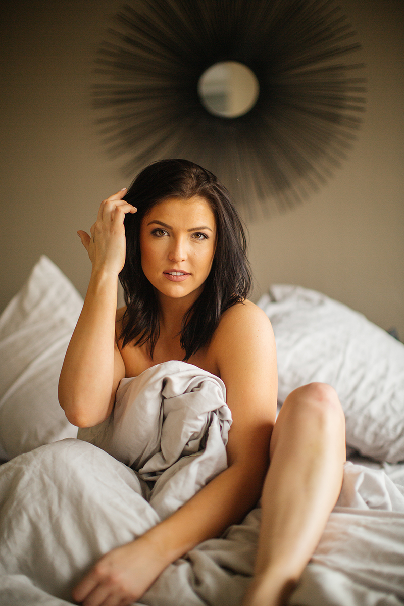 A beautiful young brunette woman poses topless for a Denver apartment boudoir photography session in her home in Colorado wearing black underwear sitting on on her bed with blankets