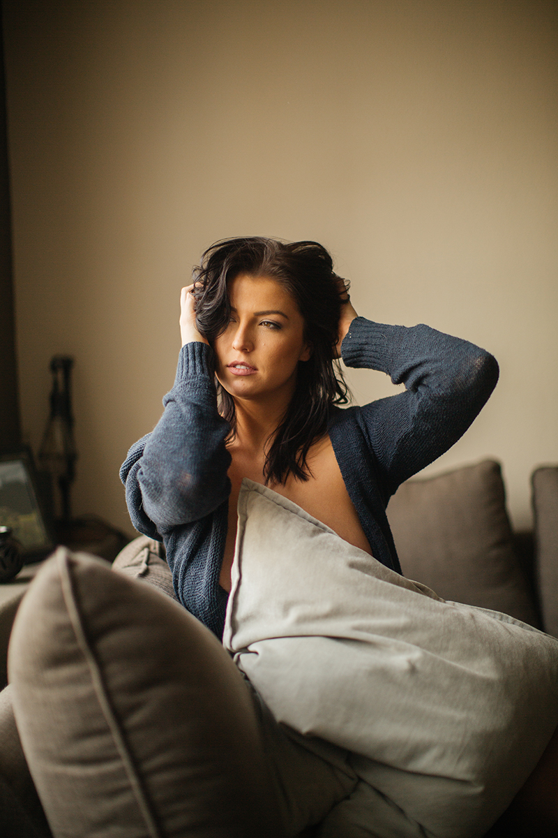 A beautiful young brunette woman poses topless for a Denver apartment boudoir photography session in her home in Colorado wearing a dark blue sweater with gray and blue underwear sitting on her couch near her window