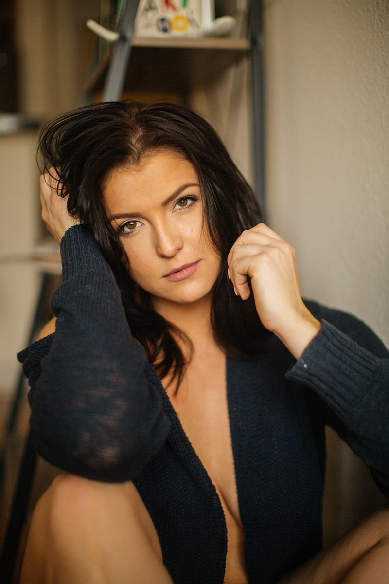 A beautiful young brunette woman poses topless for a Denver apartment boudoir photography session in her home in Colorado wearing a dark blue sweater with gray and blue underwear sitting on the floor