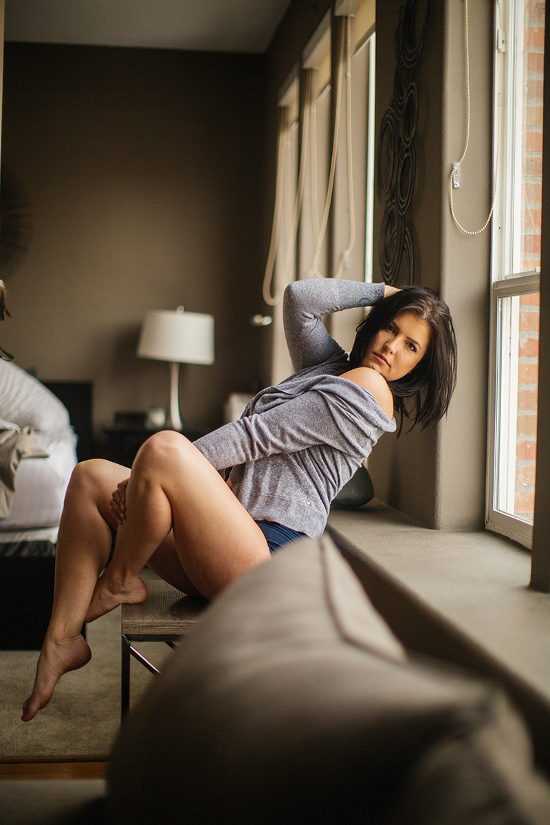 A beautiful young brunette woman poses topless for a Denver apartment boudoir photography session in her home in Colorado wearing a gray sweater with black underwear sitting on her couch near her window