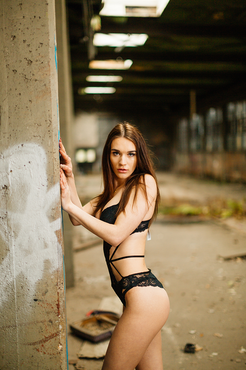 A beautiful young brunette German woman poses for a Kaiserslautern couples boudoir photography session at an abandoned train station in Kaiserslautern leaning against a wall in front of a graffiti covered wall wearing a black lingerie body suit