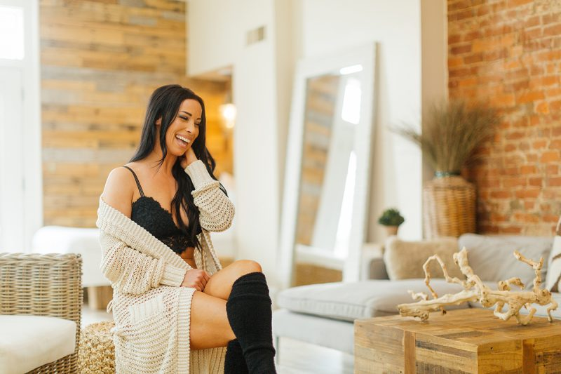 A beautiful brunette woman poses for The Gregory Two boudoir photos at an Airbnb in Cincinnati, Ohio wearing a black bra, black underwear, black knee high socks and a tan sweater sitting on a wicker stool in front of a couch