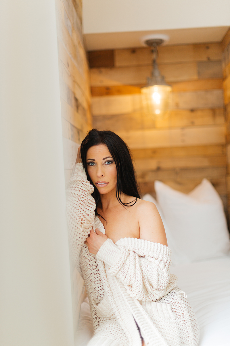 A beautiful brunette woman poses topless for The Gregory Two boudoir photos at an Airbnb in Cincinnati, Ohio wearing a black underwear, black knee high socks and a tan sweater sitting on white couch
