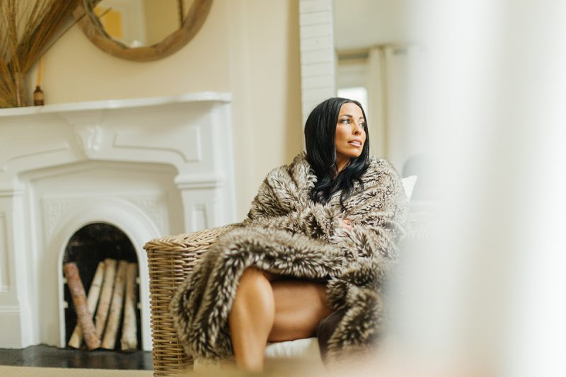 A beautiful brunette woman poses for The Gregory Two boudoir photos at an Airbnb in Cincinnati, Ohio wearing a red bra and a fur blanket sitting on a wicker chair next to a window with a mirror behind her