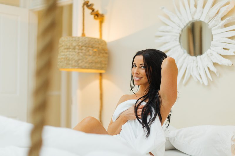 A beautiful brunette woman poses nude for The Gregory Two boudoir photos at an Airbnb in Cincinnati, Ohio on a white bed wrapped up in the sheets