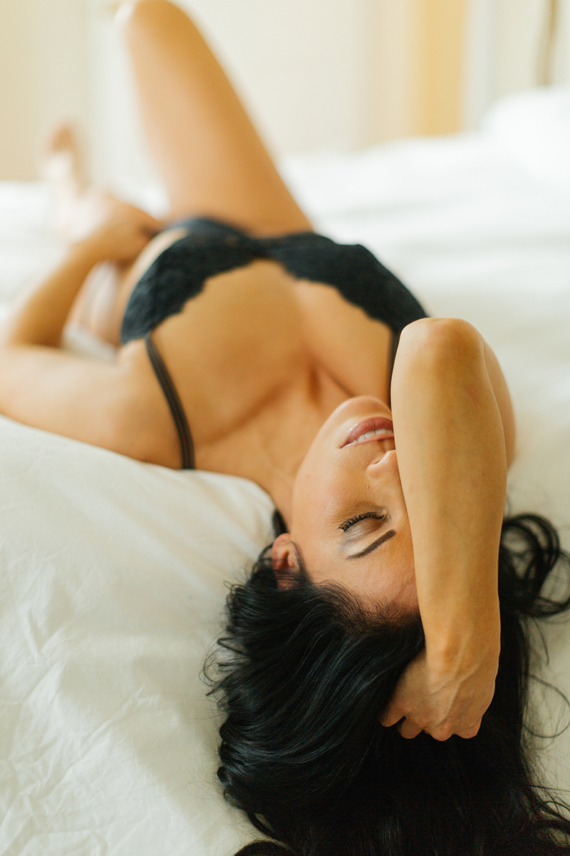 A beautiful brunette woman poses for The Gregory Two boudoir photos at an Airbnb in Cincinnati, Ohio wearing a black bra and underwear set laying on a white bed