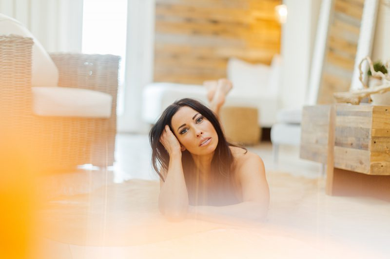 A beautiful brunette woman poses nude for The Gregory Two boudoir photos at an Airbnb in Cincinnati, Ohio laying on a fur rug on the floor