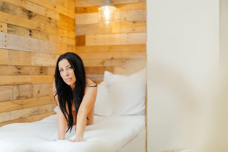 A beautiful brunette woman poses nude for The Gregory Two boudoir photos at an Airbnb in Cincinnati, Ohio crawling on a white couch