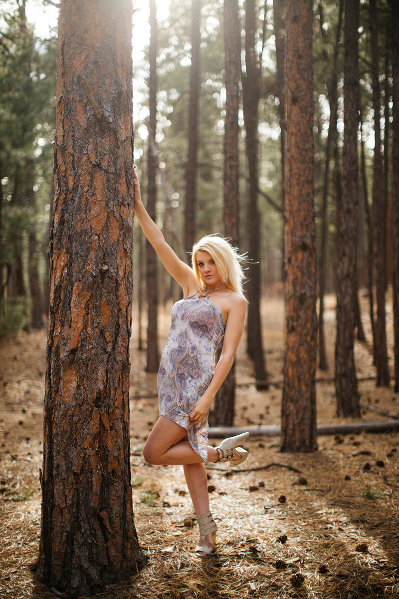 A beautiful young blonde woman poses for a Fox Run Regional Park boudoir photography session in Black Forest near Colorado Springs, CO wearing a blue and purple dress leaning against a tree in a forest