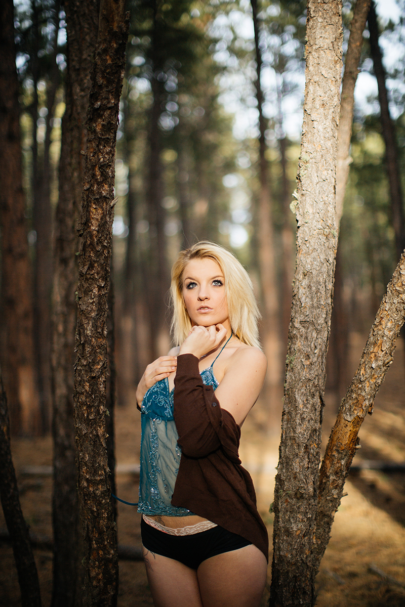 A beautiful young blonde woman poses for a Fox Run Regional Park boudoir photography session in Black Forest near Colorado Springs, CO wearing black underwear, teal lingerie and a brown sweater standing in the light of a thick forest