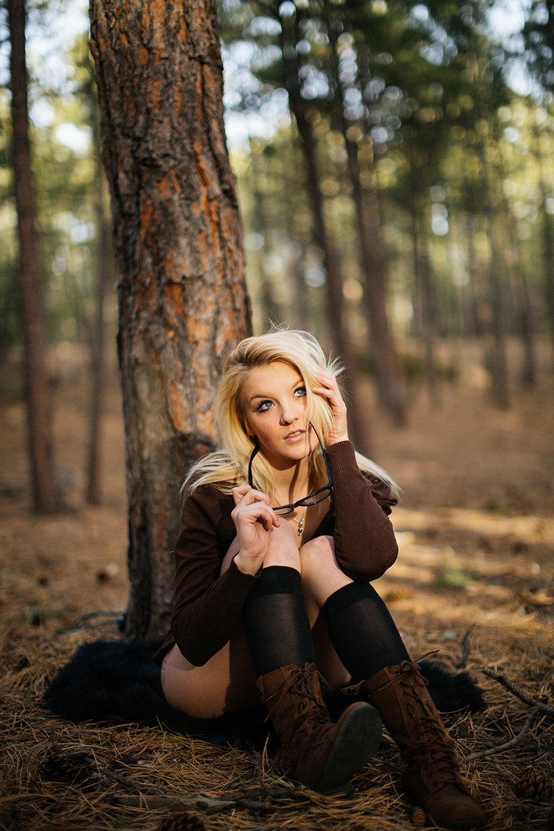 A beautiful young blonde woman poses for a Fox Run Regional Park boudoir photography session in Black Forest near Colorado Springs, CO wearing a brown sweater, black glasses and black knee high socks sitting on a blanket next to a tree in a forest