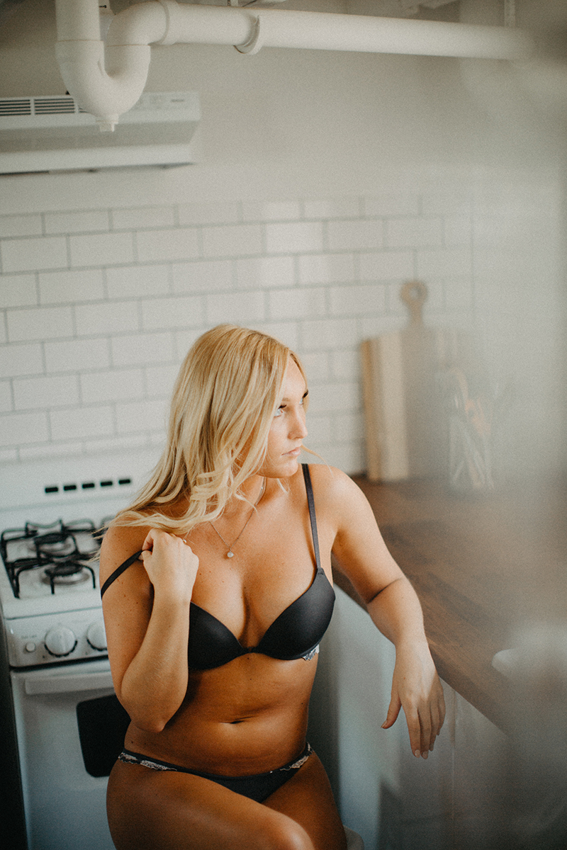 A beautiful young blonde woman poses for a Warwick Airbnb boudoir photography session in a cottage wearing a gray bra and underwear set in the kitchen in Rhode Island