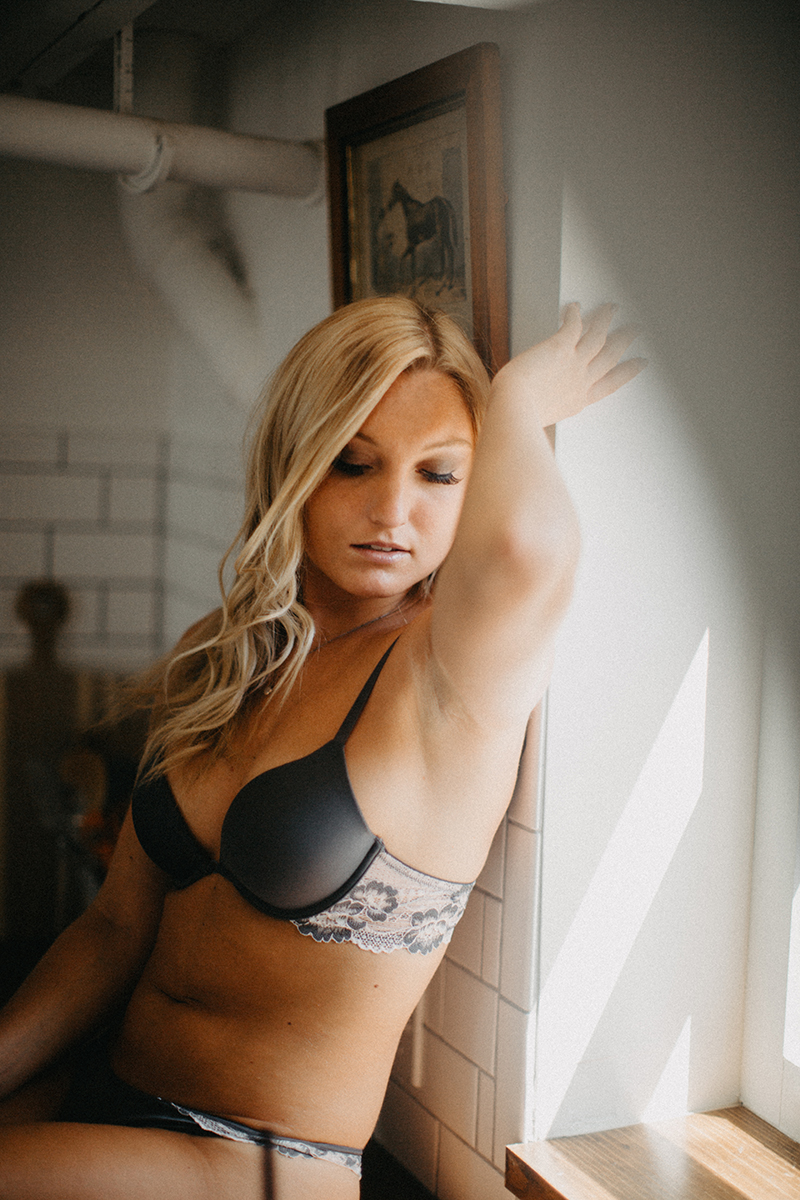 A beautiful young blonde woman poses for a Warwick Airbnb boudoir photography session in a cottage wearing a gray bra and underwear set sitting on the counter in the kitchen in Rhode Island