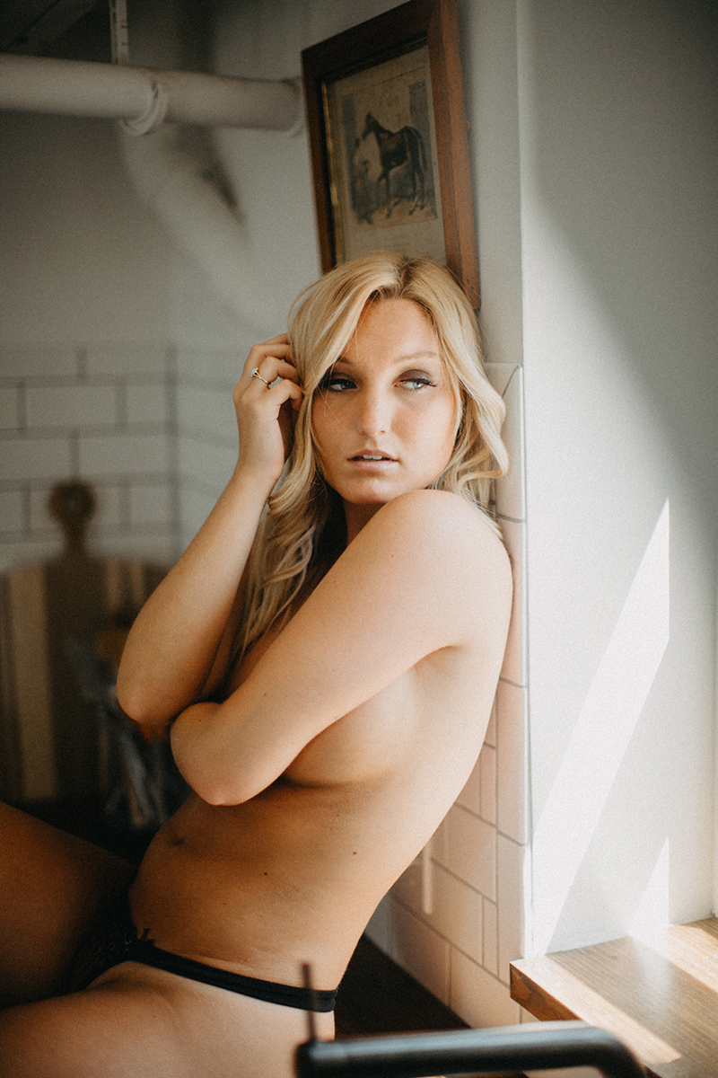 A beautiful young blonde woman poses topless for a Warwick Airbnb boudoir photography session in a cottage wearing gray underwear set in the kitchen in Rhode Island