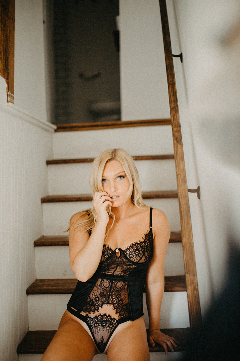 A beautiful young blonde woman poses for a Warwick Airbnb boudoir photography session in a cottage wearing black lingerie and underwear on the stairs in Rhode Island