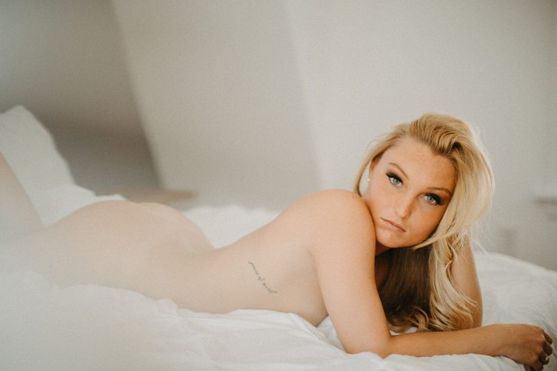 A beautiful young blonde woman poses nude for a Warwick Airbnb boudoir photography session in a cottage on a bed in Rhode Island