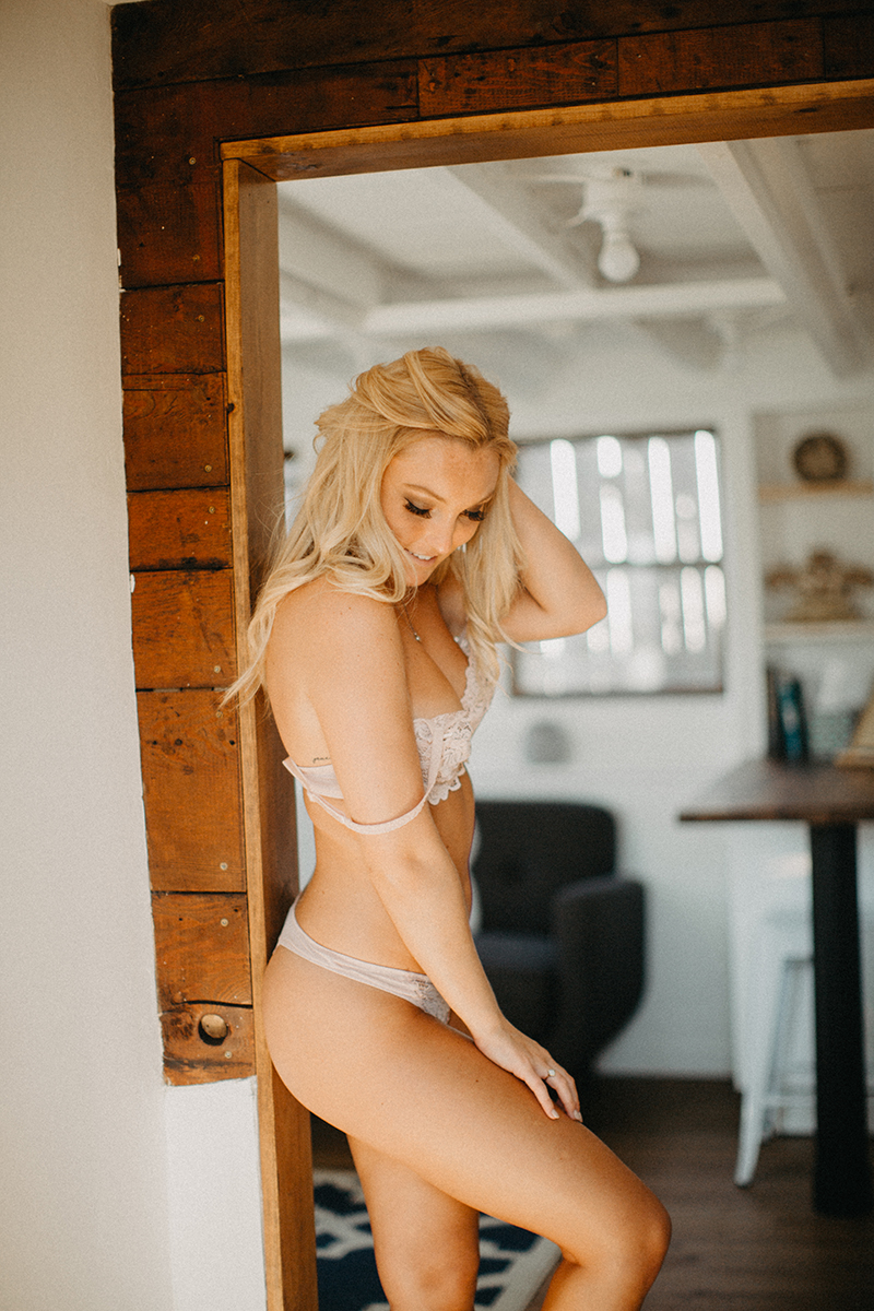 A beautiful young blonde woman poses for a Warwick Airbnb boudoir photography session wearing a white bra and underwear set in a doorway in a cottage on a bed in Rhode Island