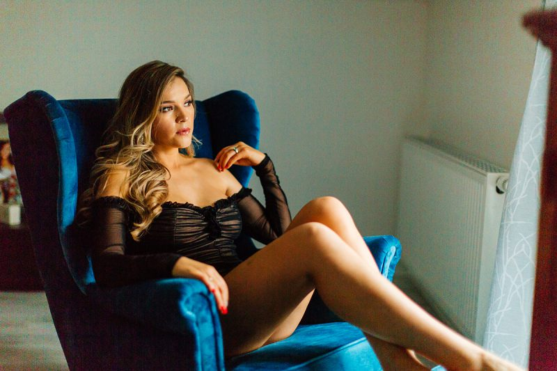 A beautiful woman poses in black lingerie in a dim room on her blue chair for our first milk bath boudoir photography session in Mehlingen near Kaiserslautern, Germany