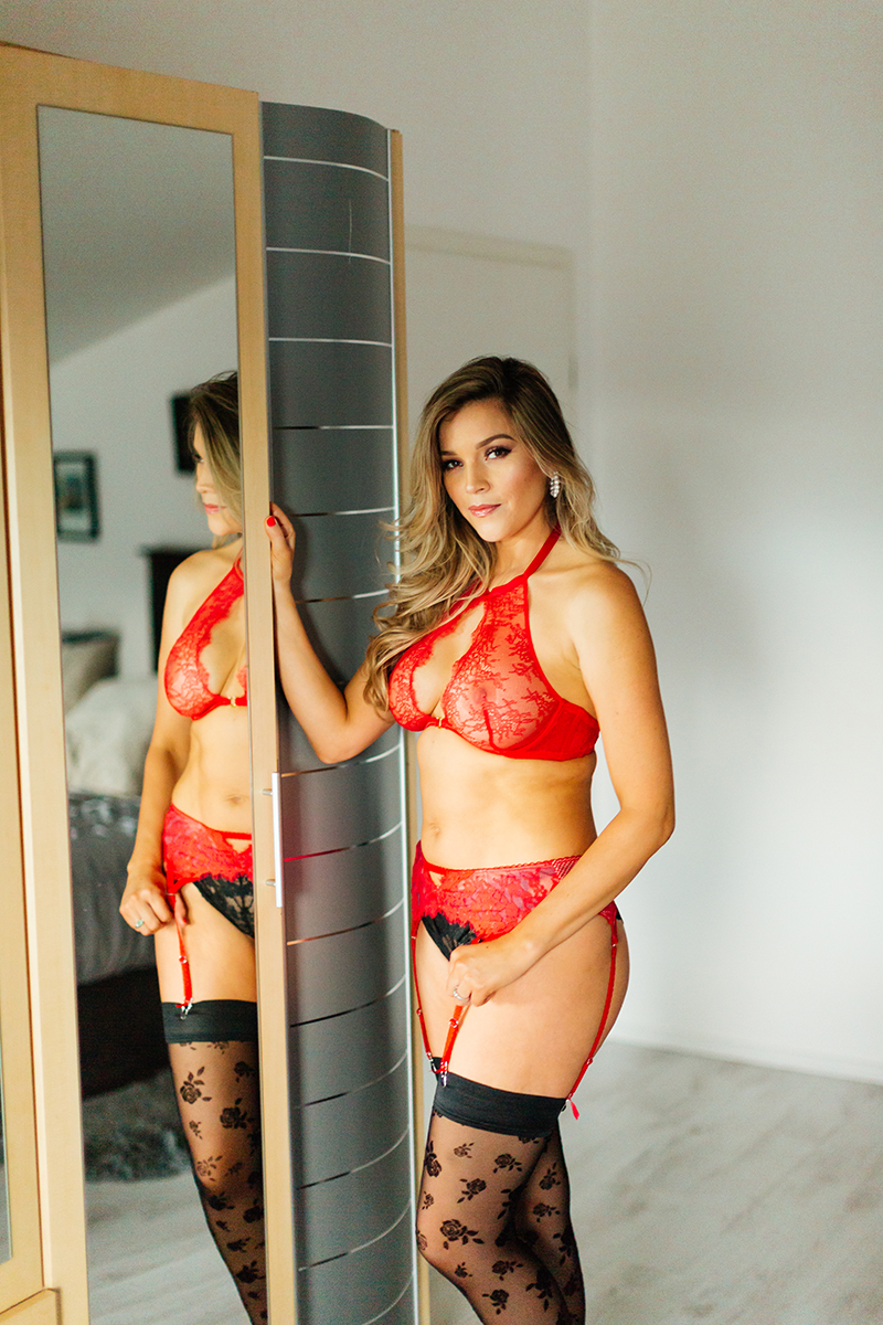 A beautiful woman poses in red lingerie and black stockings next to the mirror of her wardrobe for our first milk bath boudoir photography session in Mehlingen near Kaiserslautern, Germany