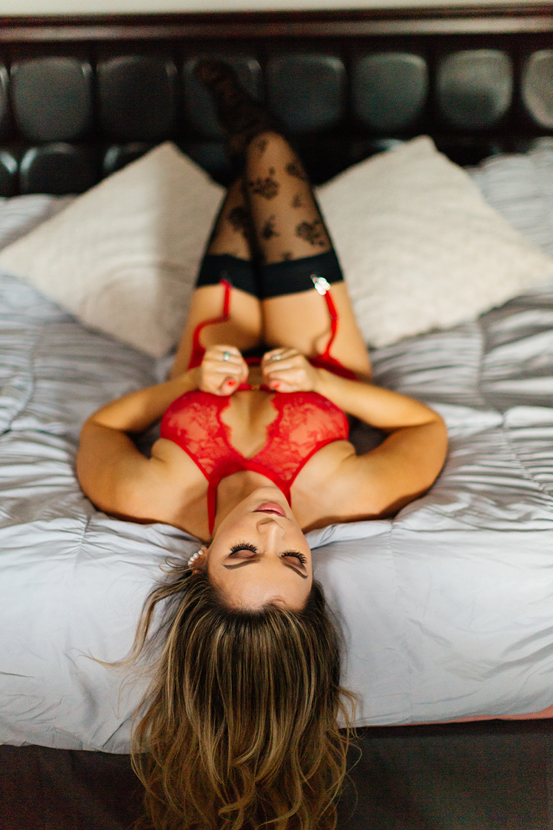 A beautiful woman poses in red lingerie and black stockings on her bed for our first milk bath boudoir photography session in Mehlingen near Kaiserslautern, Germany