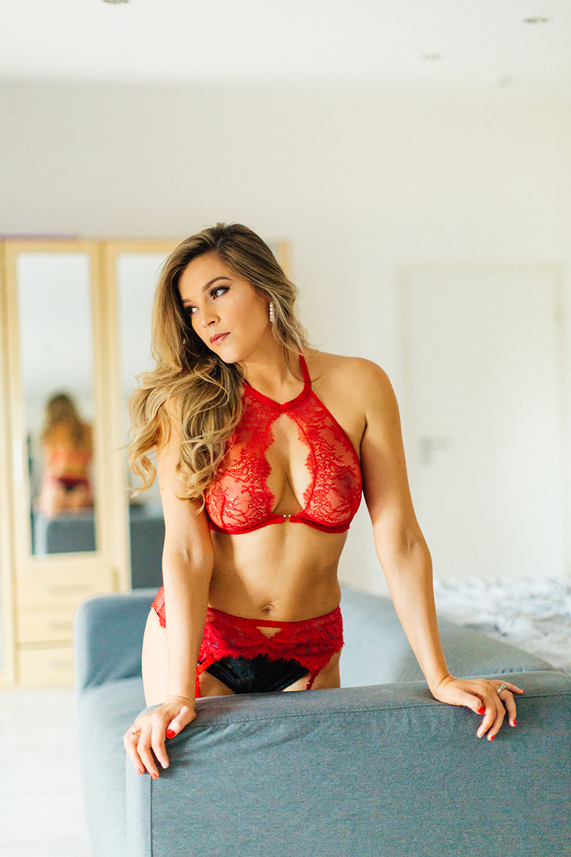 A beautiful woman poses in red lingerie and black stockings on a couch in her bedroom for our first milk bath boudoir photography session in Mehlingen near Kaiserslautern, Germany