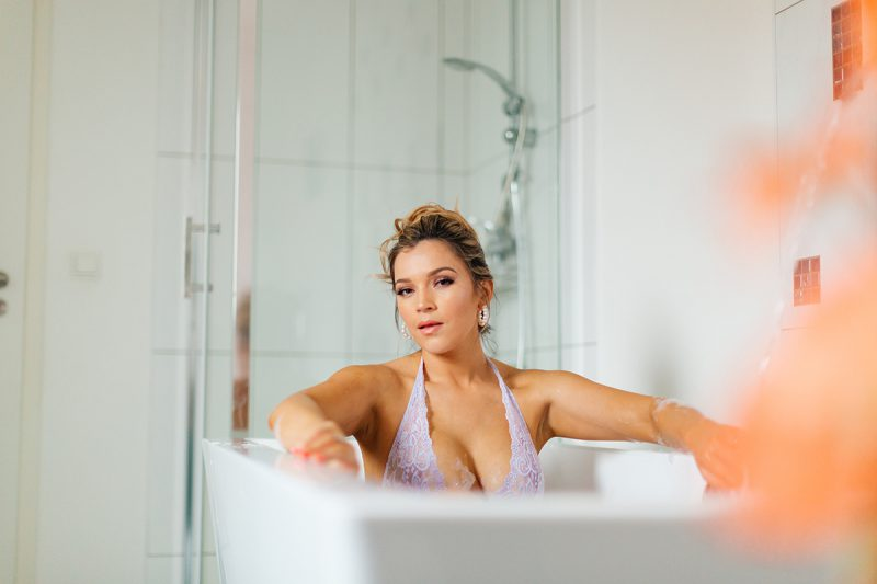 A beautiful woman poses in lavender lingerie while sitting in her bathtub for our first milk bath boudoir photography session in Mehlingen near Kaiserslautern, Germany