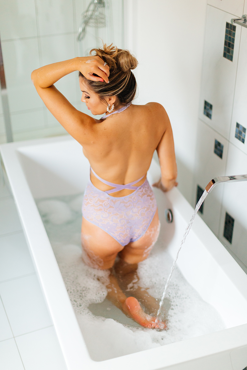 A beautiful woman poses in lavender lingerie while kneeling in her bathtub for our first milk bath boudoir photography session in Mehlingen near Kaiserslautern, Germany