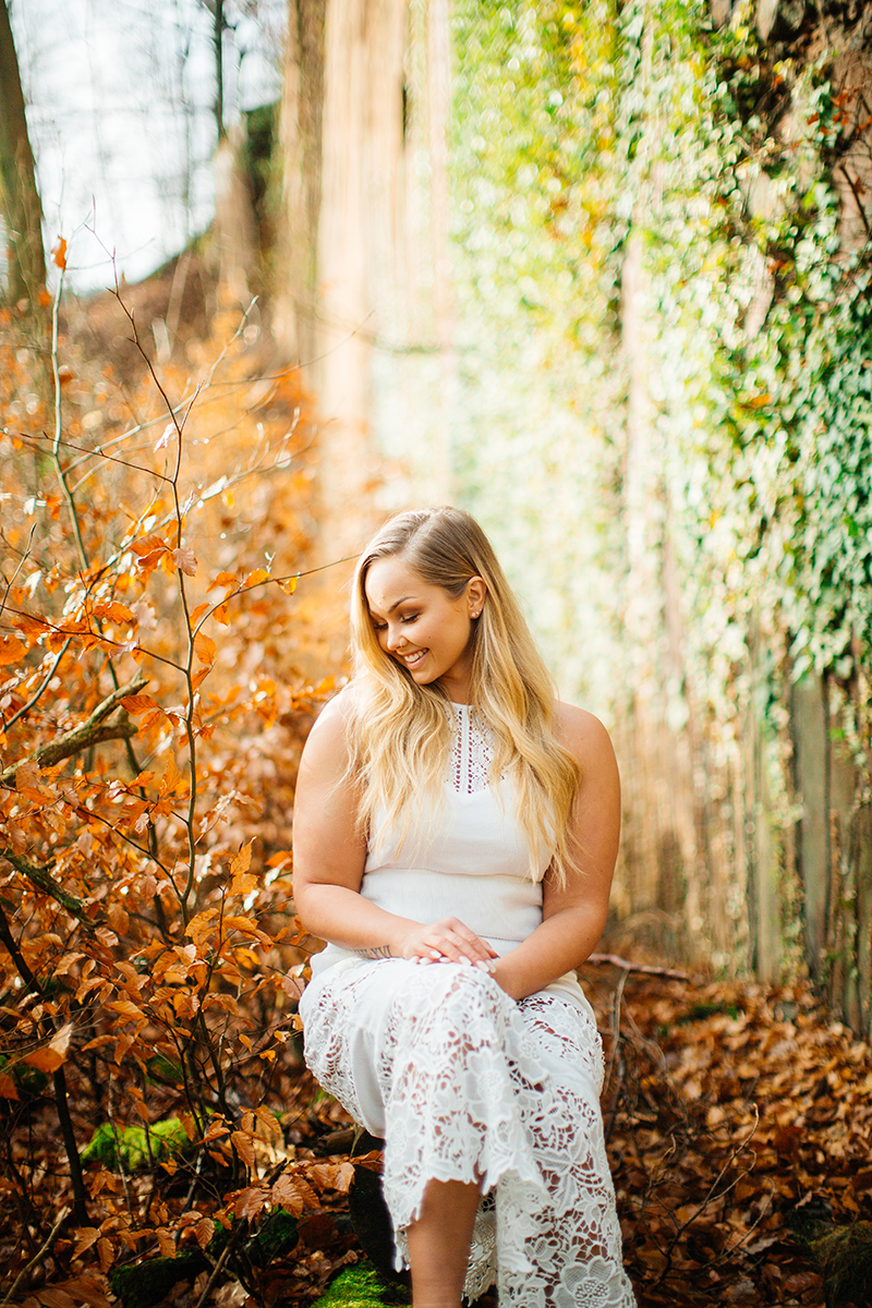 A beautiful young blonde woman wearing a white dress sitting in front of a rock wall covered in vines with fall colors behind her for a Hardenburg Castle boudoir photography session in Bad Dürkheim, Germany