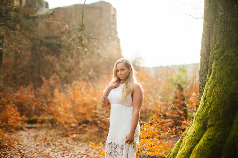 A beautiful young blonde woman wearing a white dress posing in front of the remains of a castle with fall colors behind her for a Hardenburg Castle boudoir photography session in Bad Dürkheim, Germany