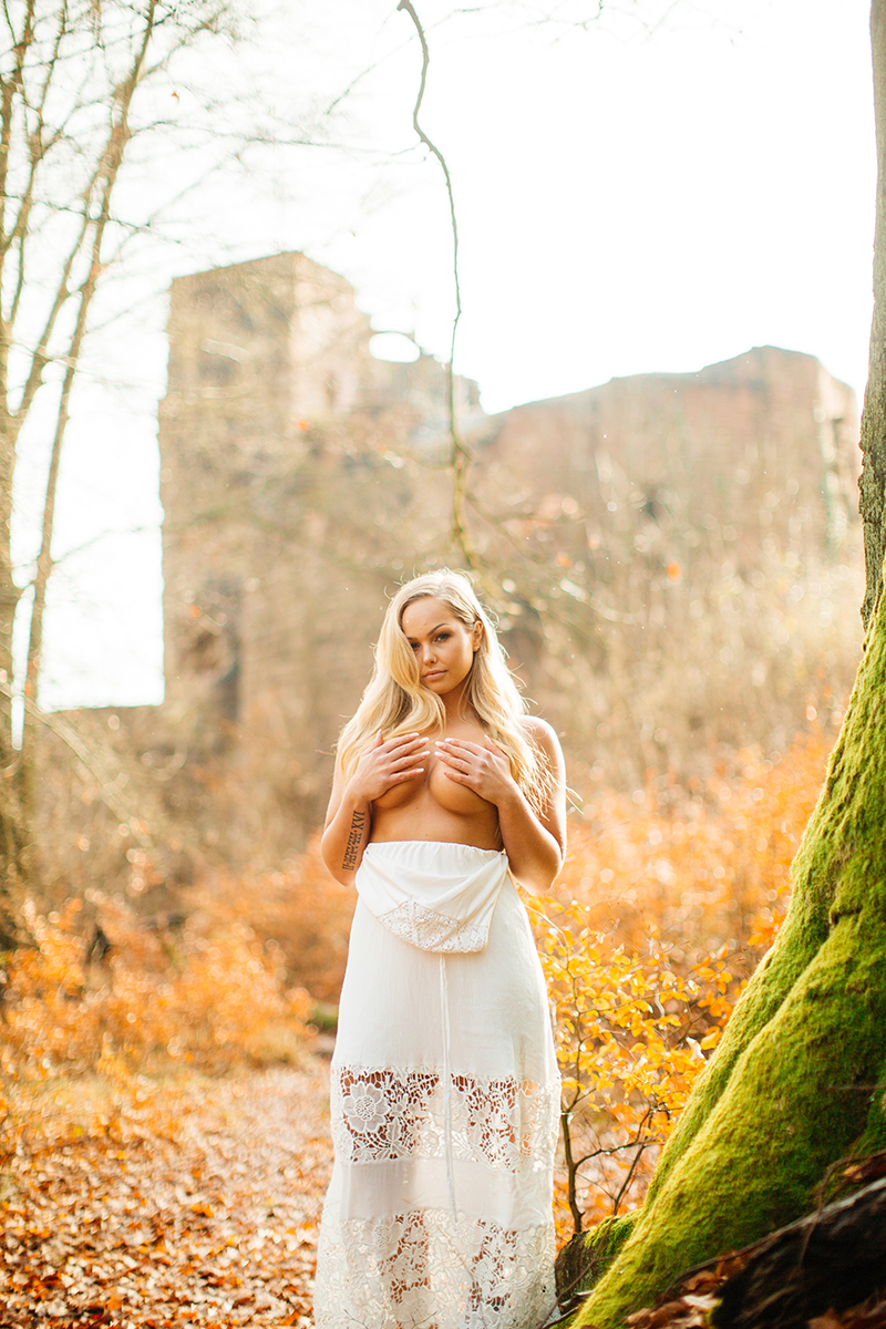A beautiful young blonde woman topless wearing a white dress posing in front of the remains of a castle with fall colors behind her for a Hardenburg Castle boudoir photography session in Bad Dürkheim, Germany