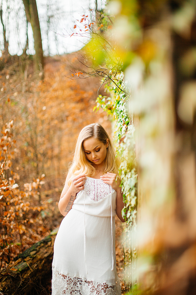 A beautiful young blonde woman wearing a white dress leaning against a rock wall covered in vines with fall colors behind her for a Hardenburg Castle boudoir photography session in Bad Dürkheim, Germany