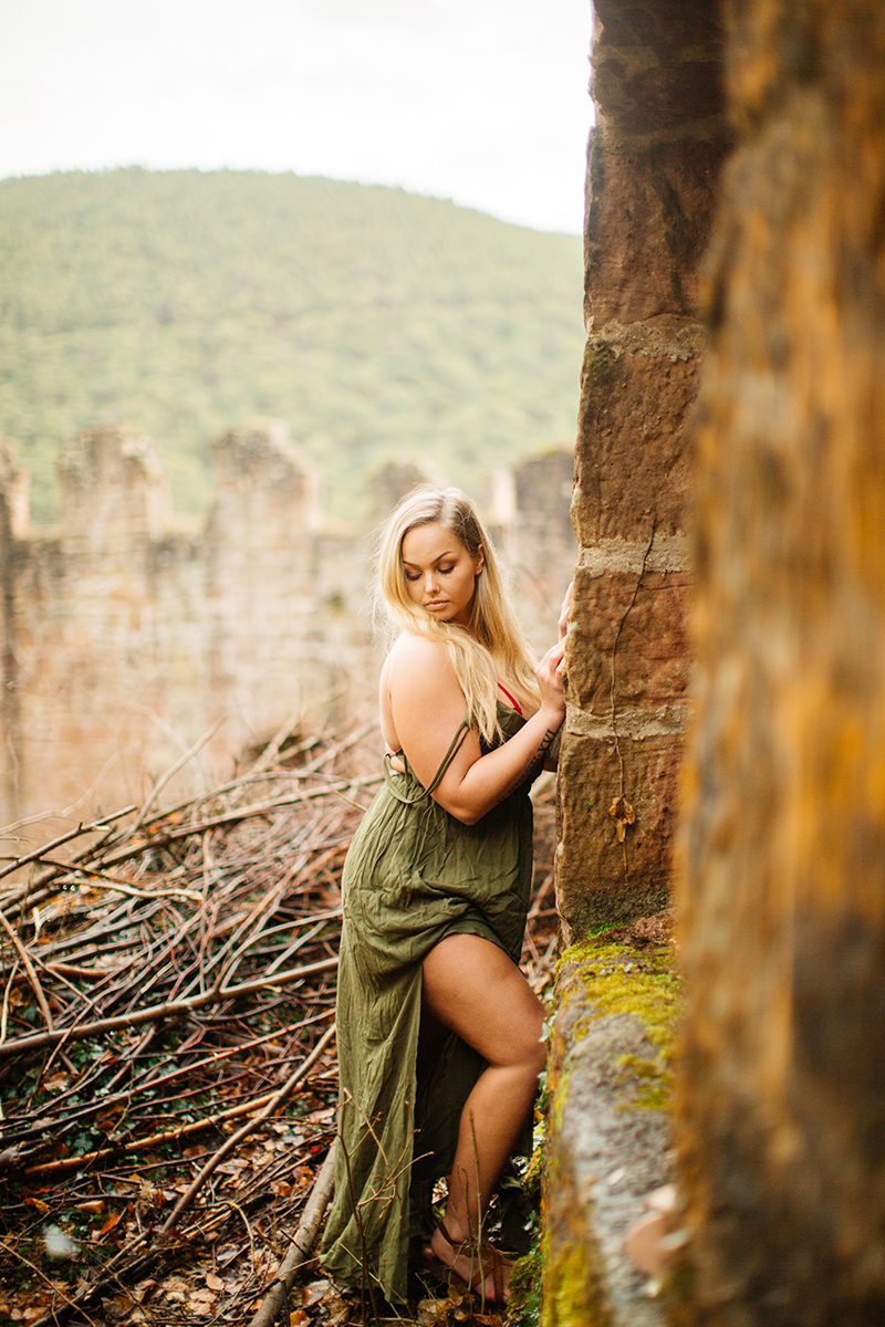 A beautiful young blonde woman wearing a green dress leaning on the remains of a castle with fall colors behind her for a Hardenburg Castle boudoir photography session in Bad Dürkheim, Germany